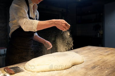 chef or baker making bread dough at bakery
