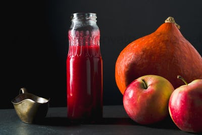 Cranberry sauce in a bottle, pumpkin and apples on a table side view