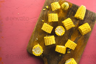 Different pieces of fresh corn on a wooden cutting board