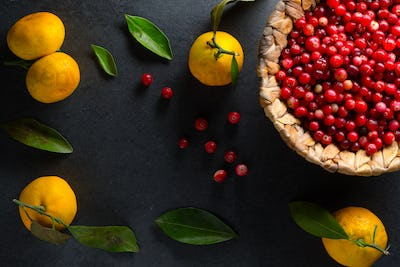 Yellow mandarins with leaves and cranberries in a basket on a gray stone free space