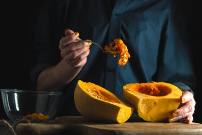 Spoon with seeds in a hand, pumpkin halves on a table on a blue background