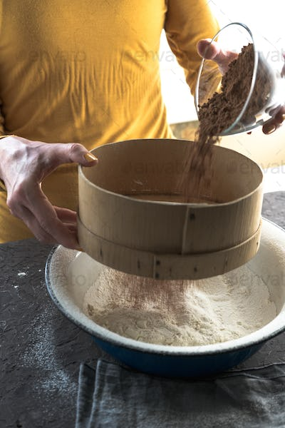 Cocoa is poured from a bowl into a sieve