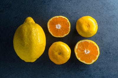 Four halves of an orange and a lemon on a blue stone