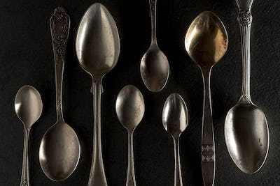 Different spoons on a black stone close-up