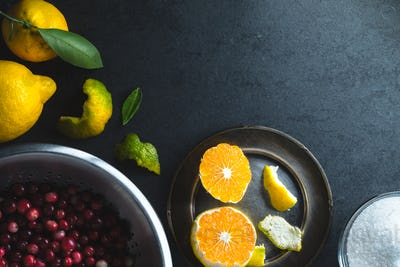 Cranberries in a bowl, tangerines and lemon in the left corner of the table