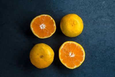 Four halves of an orange on a blue stone