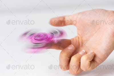close up of hand playing with fidget spinner