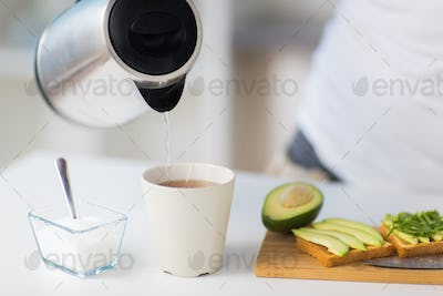 kettle pouring hot water to tea cup at home