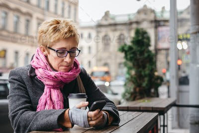 Woman browsing phone in outside cafe