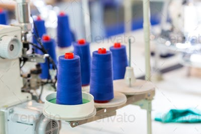 Spools of threads on sewing machine, cloth factory