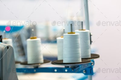 Spools of white threads on sewing machine, closeup