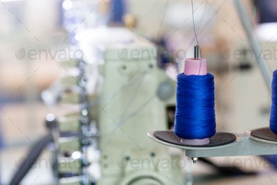 Spools of blue threads on sewing machine, factory