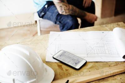 Smartphone blueprint and hard helmet on wooden table
