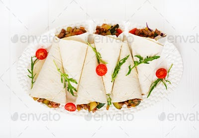 Burritos wraps with beef and vegetables on a light  background. Flat lay. Top view