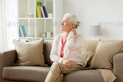 senior woman suffering from neck pain at home