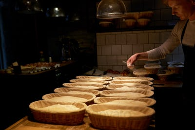 baker with baskets for dough rising at bakery