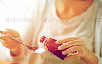 woman pouring medicine from bottle to spoon