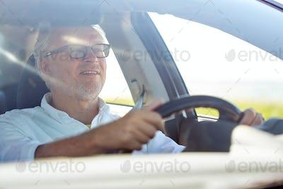 happy senior man in glasses driving car
