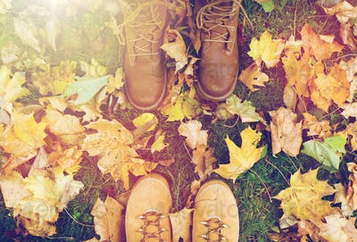 couple of feet in boots and autumn leaves