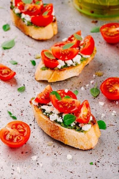 bruschetta with pesto  sauce, feta cheese, tomatoes and basil