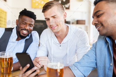 male friends with smartphone drinking beer at bar