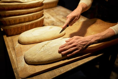 baker making bread and cutting dough at bakery