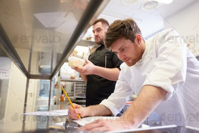 chef and cook with lists or bills at kitchen