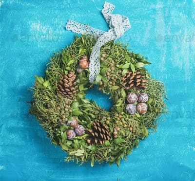 Christmas decorative wreath with pine cones over blue wall background