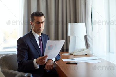 businessman with papers working at hotel room