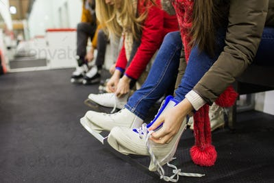 close up of woman putting on ice skates
