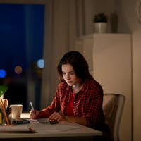 student girl with notebook and calculator at home