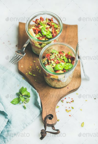 Healthy salad with quionoa, avocado, dried tomatoes on wooden board