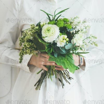 Young woman wearing white clothes holding bouquet. Square crop