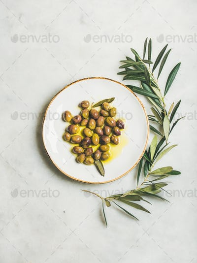 Pickled green Mediterranean olives in virgin olive oil on plate