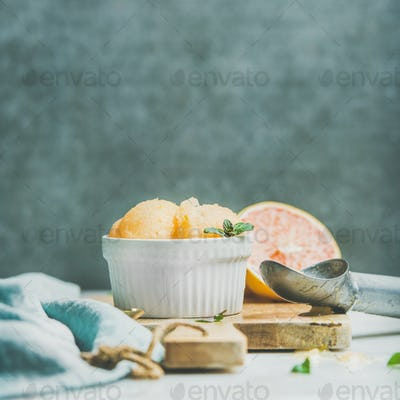 Pink grapefruit sorbet with mint in bowl on wooden board