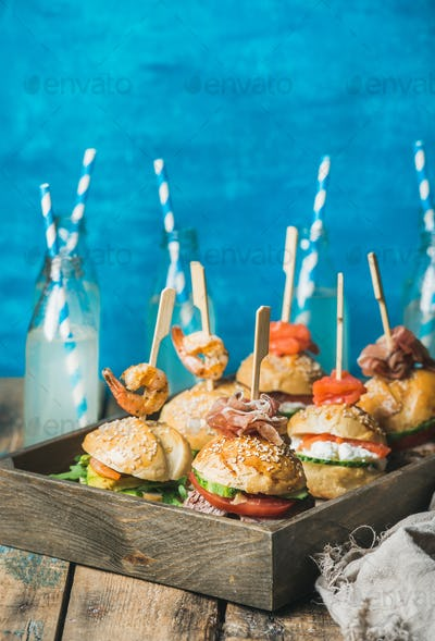 Homemade burgers in wooden tray and lemonade in glass bottles