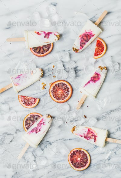 Blood orange, yogurt and granola popsicles on ice cubes