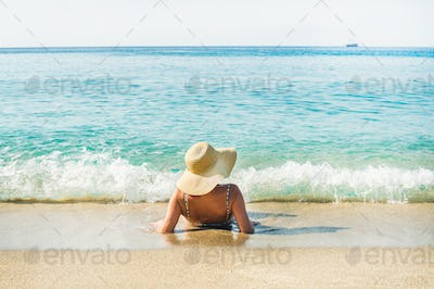 Woman lying on sand and enjoying clear blue sea waters