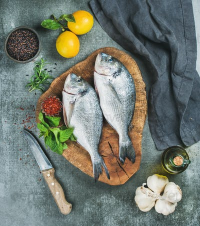 Uncooked sea bream fish with lemon, herbs, spices, olive oil