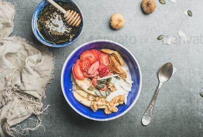 Yogurt, granola, seeds, berry and honey in blue ceramic bowl