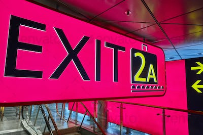 Exit information signal post at airport terminal. Travel background. Horizontal