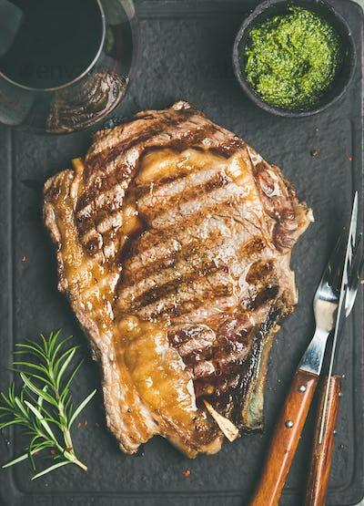 Grilled hot rib-eye beef steak on bone and red wine