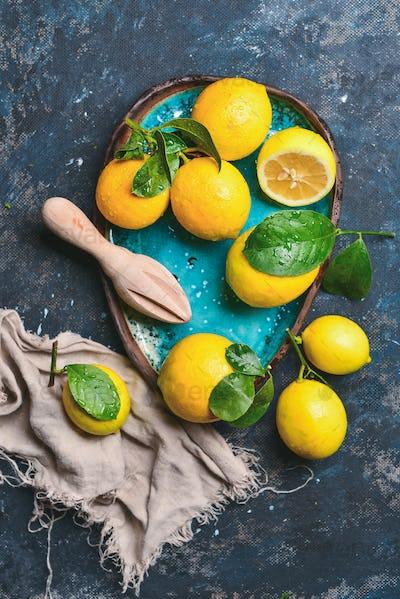 Freshly picked orange lemons with leaves in blue ceramic plate