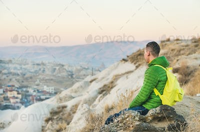 Young man sitting at edge of cliff, Cappadocia, Central Turkey