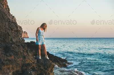 Young blond woman looking at still water, Alanya, Turkey