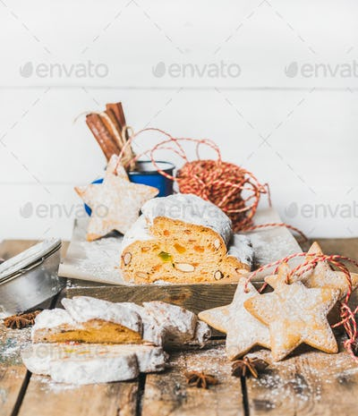 Piece of Traditional German Christmas cake Stollen with festive cookies