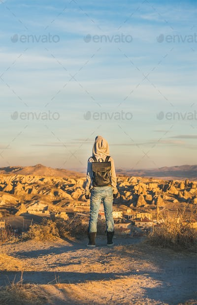 Young woman traveller standing and watching sunrise, Cappadocia, Central Turkey