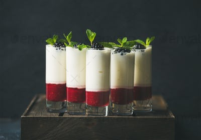 Dessert in glass with blackberries and mint over dark background