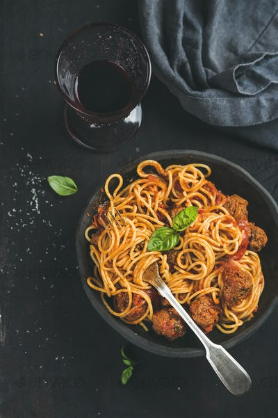 Spaghetti with meatballas, fresh green basil leaves and red wine
