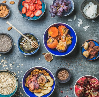Ingredients for healthy breakfast in bowls over grey stone background